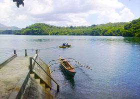 Bantay-Dagat volunteers in a motor boat passes by the wharf in Juban, Sorsogon. Another motor boat ferrying visitors is docked. (Oliver Samson)